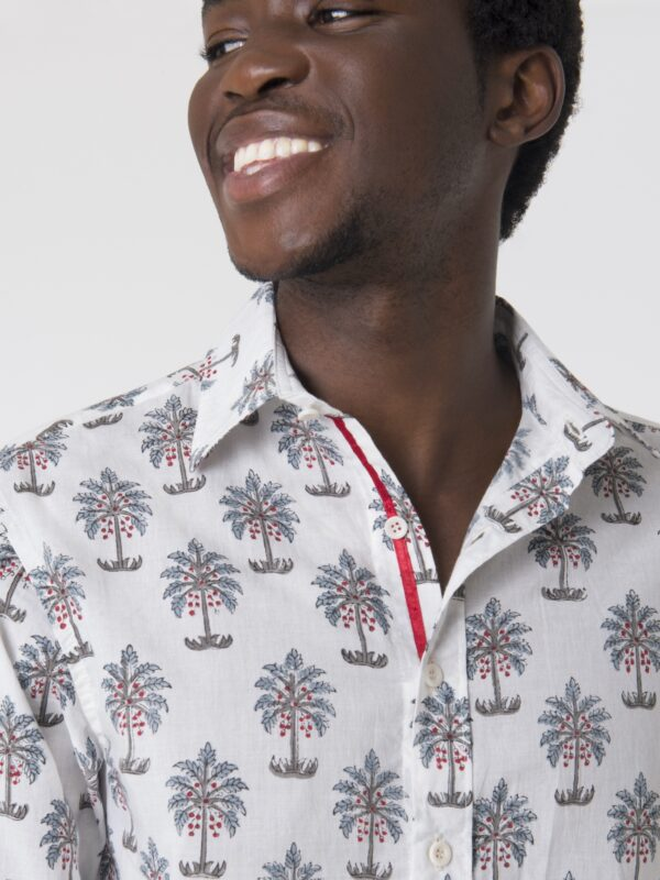 A close up shot of the collar and buttons of a block printed shirt with a tree pattern.