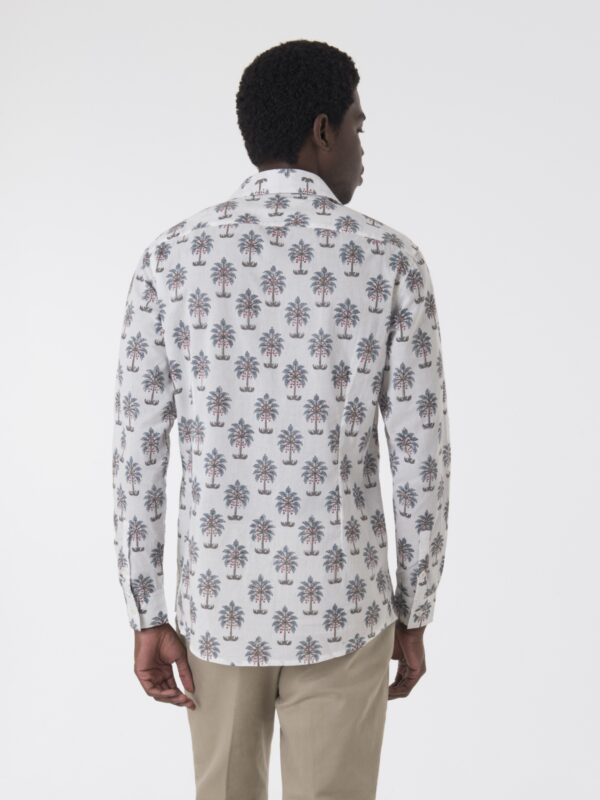 A man modelling a block printed shirt with a tree pattern walking away from the camera.