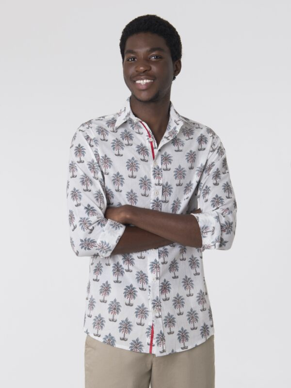 A man wearing a block printed shirt with a tree pattern with his arms folded.