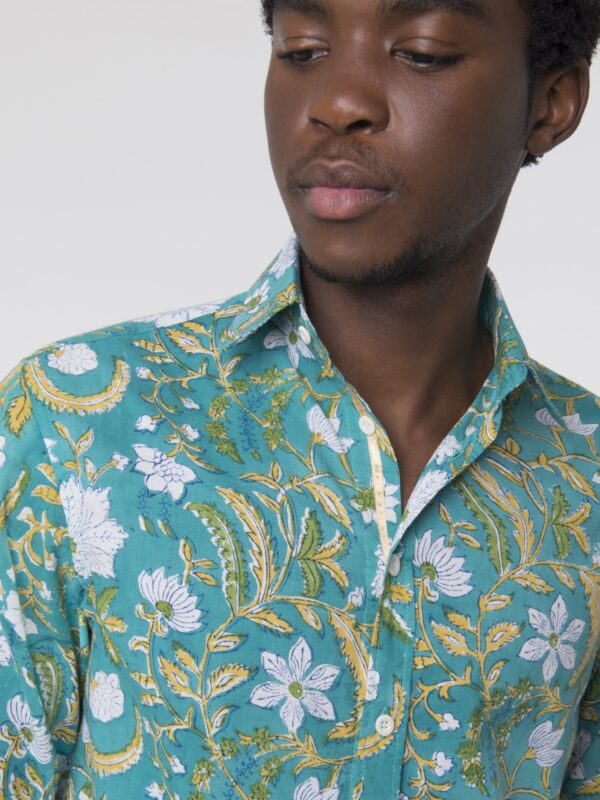 A close up shot of a man wearing a turquoise shirt with a floral printed pattern.