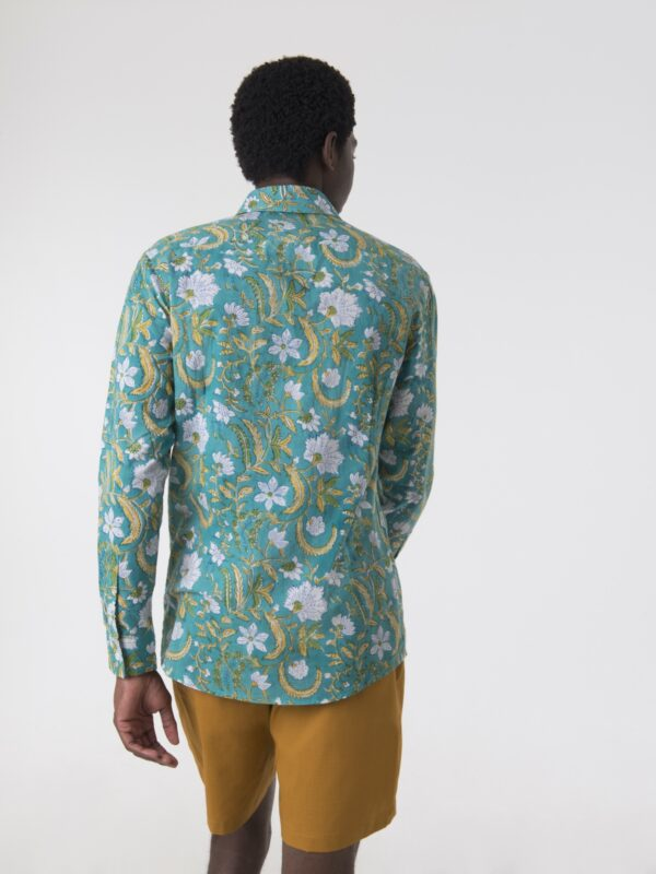 A man wearing a turquoise shirt with a floral printed pattern walking away from the camera.