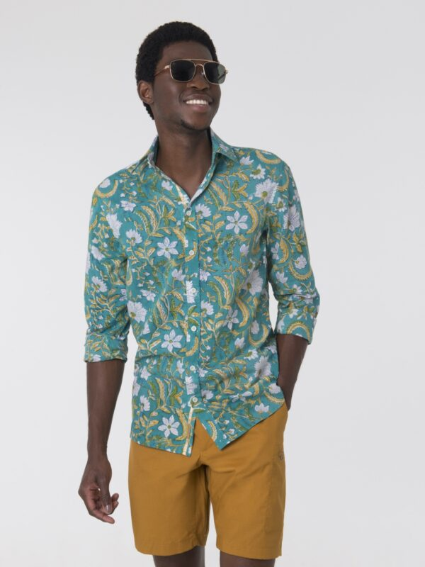 A man wearing a turquoise shirt with a floral printed pattern wearing sunglasses.