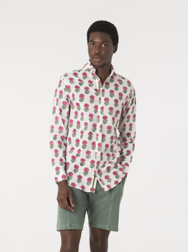 Male model front view casually wearing a white shirt with block printed red roses
