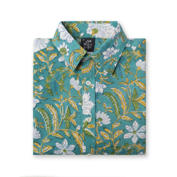 A folded turquoise shirt with a floral pattern.
