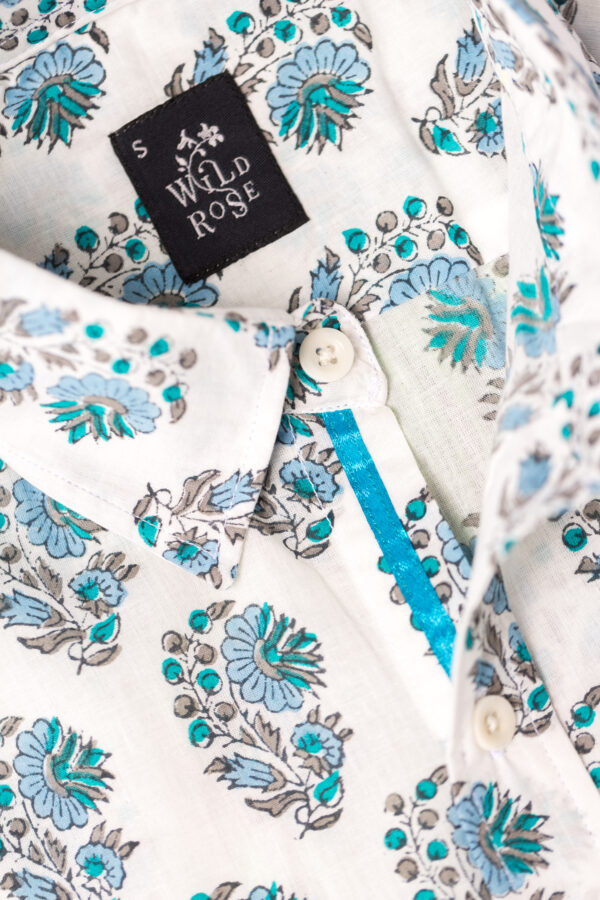 Close up of a shirt with blue and green flowers printed on its white background with Wild Rose label.