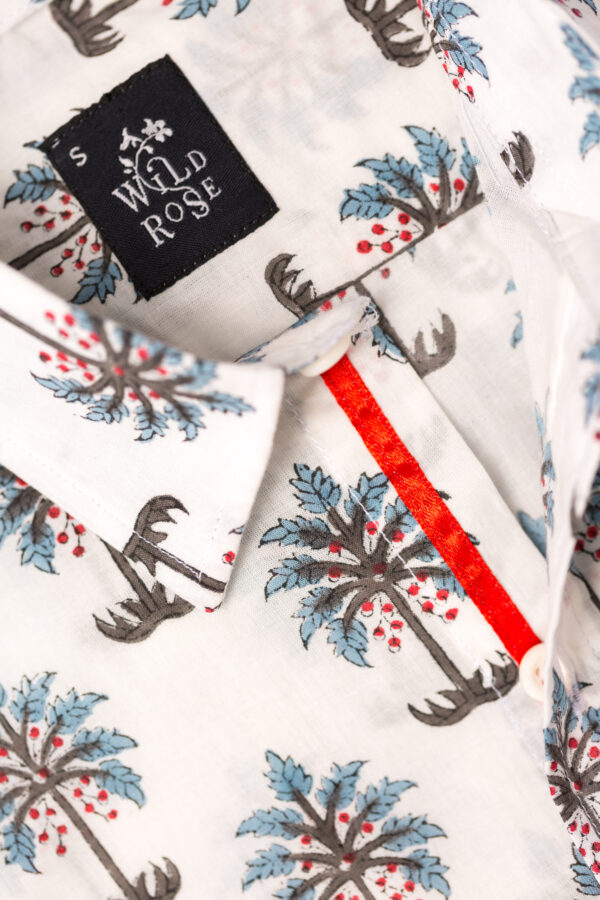 Close up of a shirt with blue and green palm tree printed on its white background with Wild Rose label.
