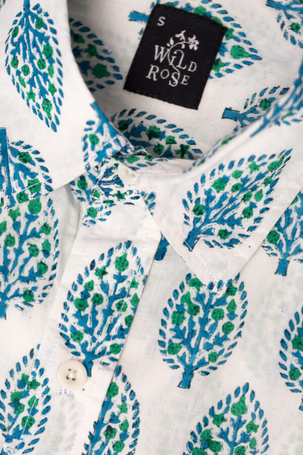 Close up of a shirt with blue and green leave printed on its white background with Wild Rose label.