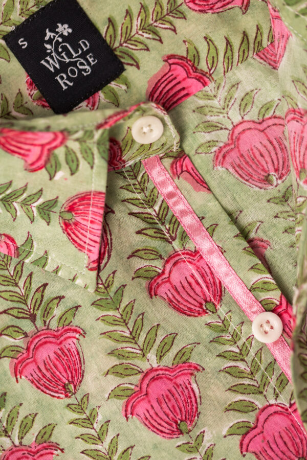 Close up of the collar on a green shirt with block printed red flowers