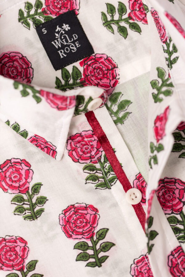Close up of the collar on a white shirt with block printed red roses