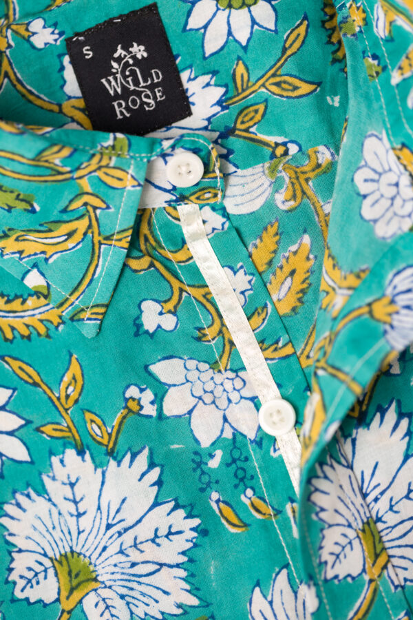 Close up of a shirt with White and green flowers printed on its teal background with Wild Rose label.
