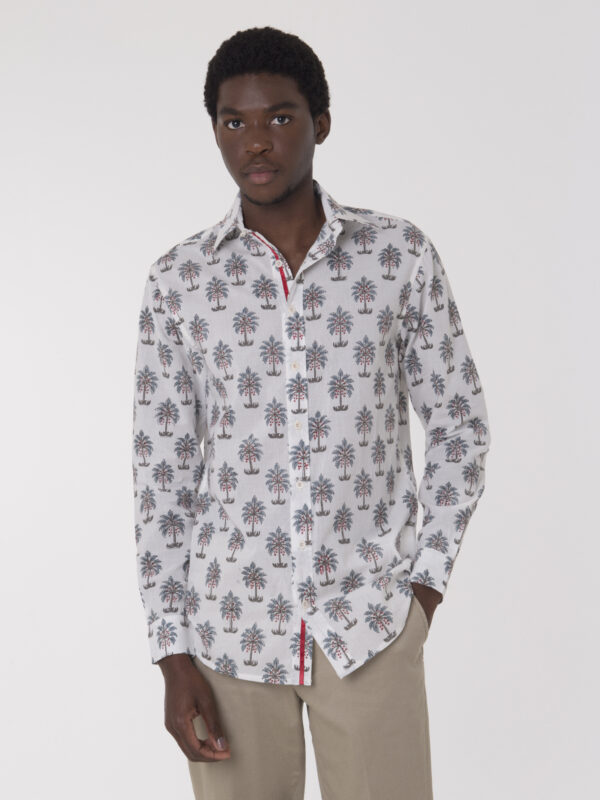 Male model wearing a white shirt with block-printed palm tree pattern