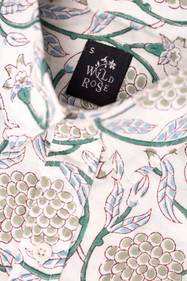 Close up of the collar on a white shirt with block printed grape plants and leaves with Wild Rose label