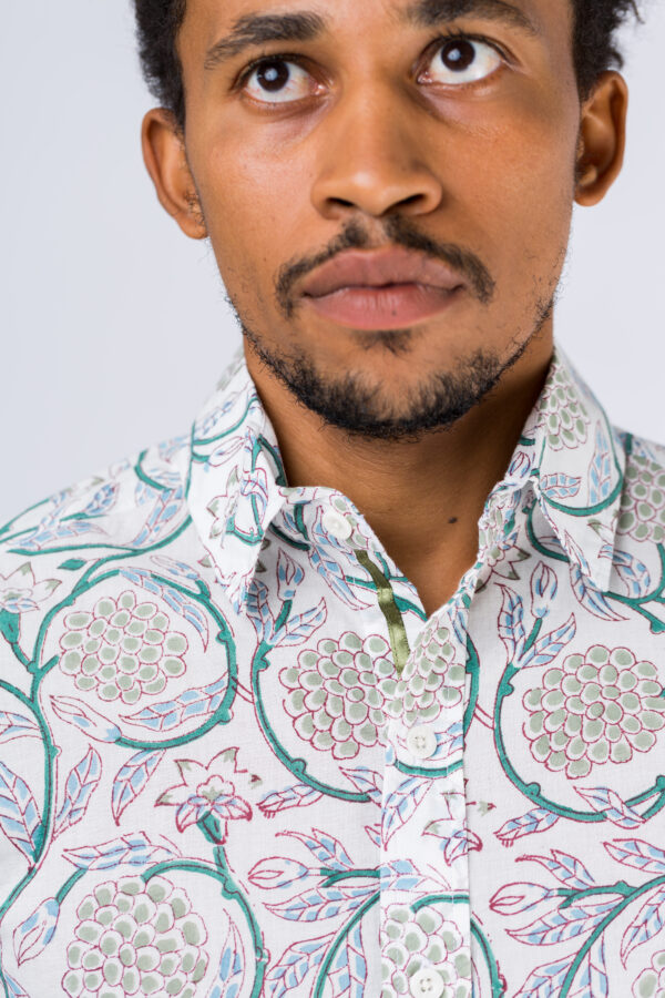 Close up of the collar on a white shirt with block printed plants and leaves on a male model.
