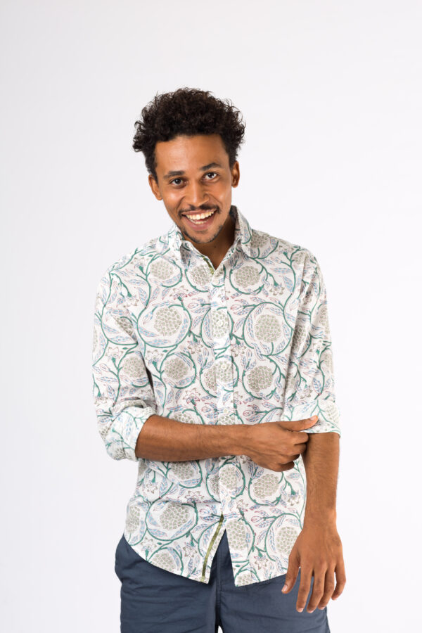 man smiling as he wears a white shirt with block printed grapes and leaves on it.