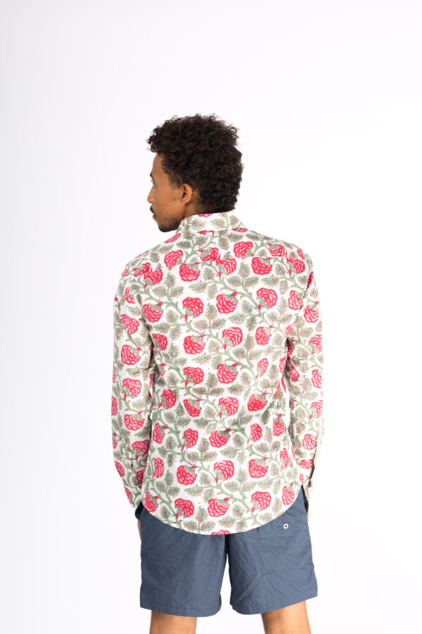Back view of a man wearing a white shirt with block printed red and green floral patterns