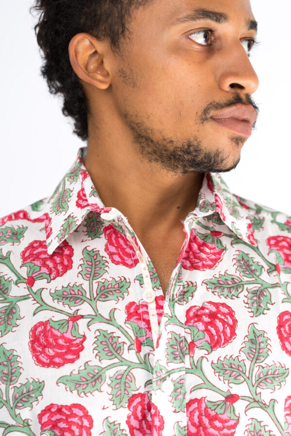 Close up of the collar on a white shirt with block printed red plants and leaves on a male model.