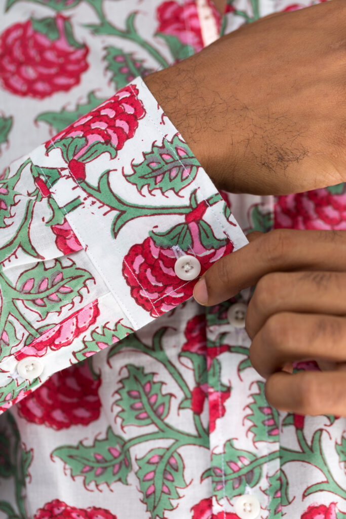 Close up of the cuff on a white shirt with block printed red and green floral pattern
