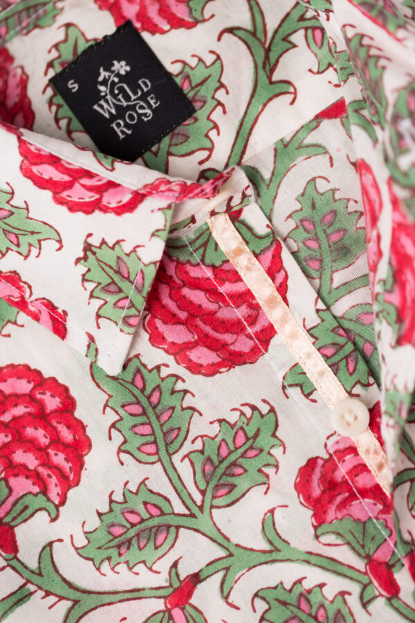 Close up of the collar and Wild Rose label on a white shirt with block printed red and green floral pattern