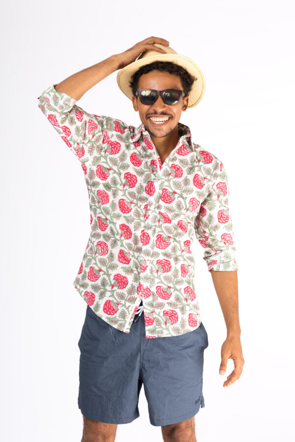 Male model in blue shorts, sunglasses and summer hat wearing a white shirt with block printed red and green floral design