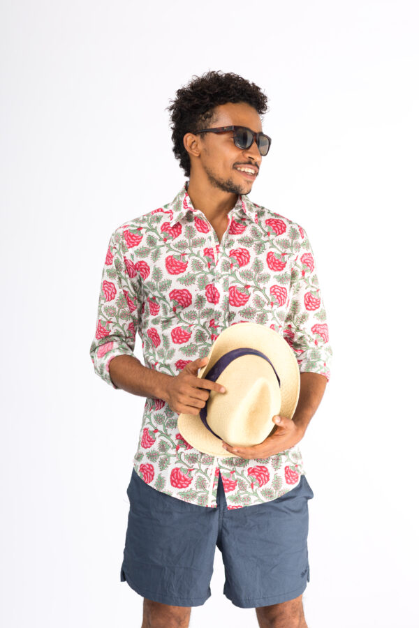 Male model in blue shorts, sunglasses holding a summer hat wearing a white shirt with block printed red and green floral design