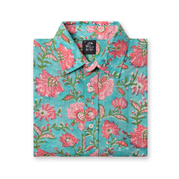 A folded turquoise shirt with floral pink and green pattern print.