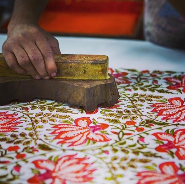 Hand block printing red flowers on to white fabric
