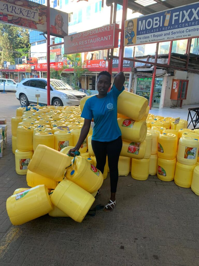 African woman standing amongst large barrels of sanitiser from Africa Yoga Project to prevent Covid19